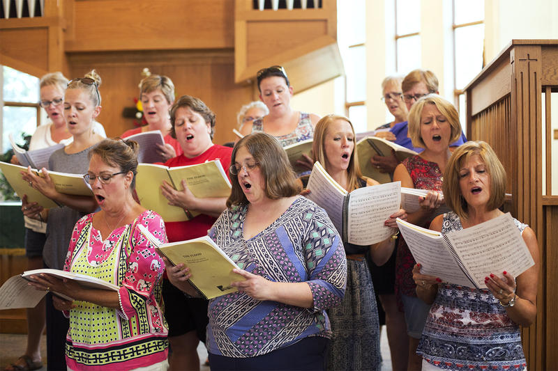 A community chorus rehearses for a performance of