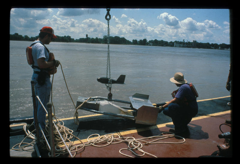 U.S. Geological Survey hydrologists Bob Holmes (right) and Rick Huizinga (left) perform an experiment on a U.S. Army Corps of Engineers barge at St. Louis on Aug. 4, 1993. Aug. 4, 1993.