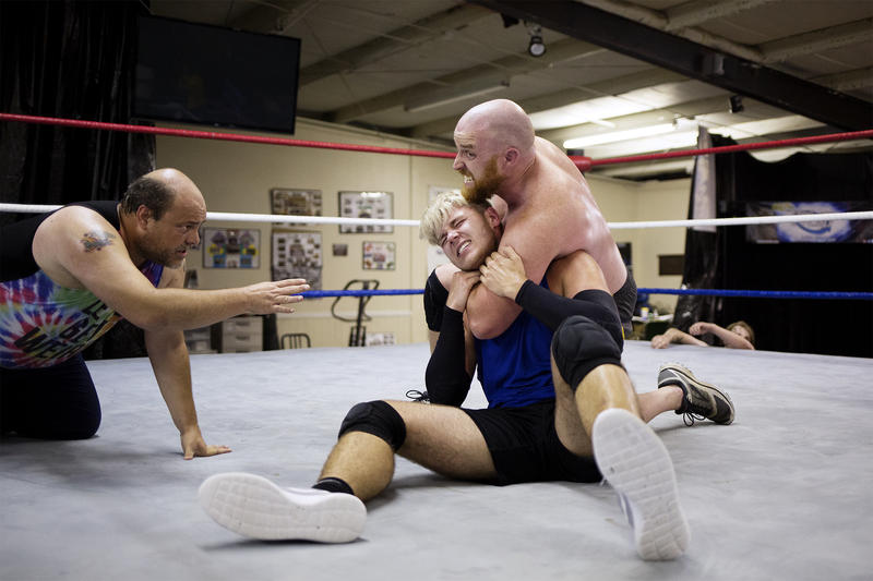 Leland Race and Gage Newton wrestle at Harley Race Wrestling Academy as Martin Kattich referees.