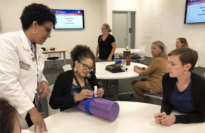 Dr. Laurie Punch, left, teaches a Stop the Bleed STL participant how to use a tourniquet to control severe bleeding.