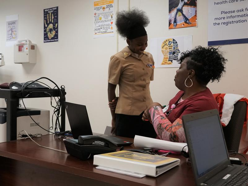 Riverview Gardens senior Shakira Bent speaks with medical assistant Ebonie Hearn-Tolliver at the makeshift student health clinic at Riverview Gardens High School. The school is renovating a campus building to serve as a full-scale clinic in the future.
