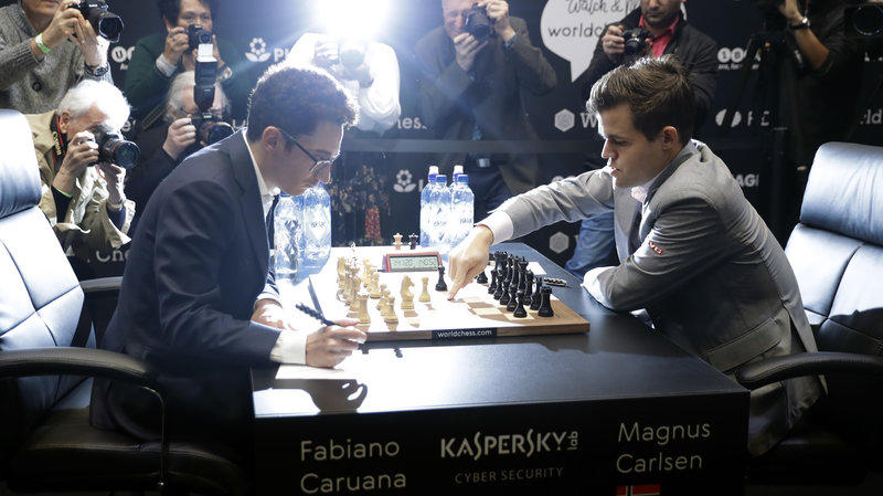 Fabiano Caruana, left, plays defending champion Magnus Carlsen in round 12 of the World Chess Championship match on Monday in London.