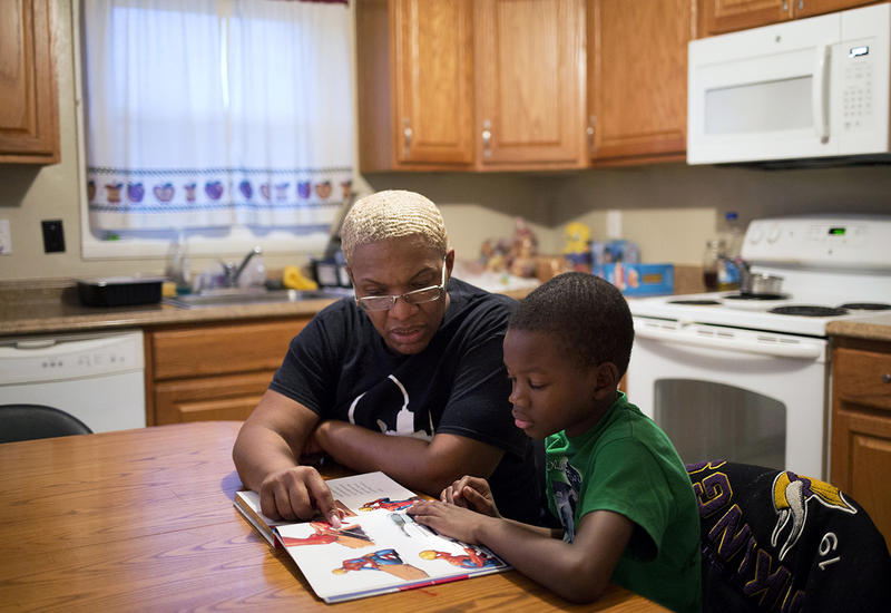 Erica Jones reads with her grandson, Jakeem, at their Florissant home. Jones has lost a daughter and a godson due to guns in recent years.