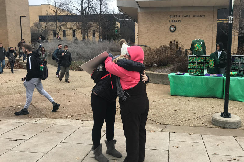 Carrie Miller (right), a member of the Rolla Mom Huggers group, hugs a student in front of the library at Missouri S&T on Dec 3, 2018.