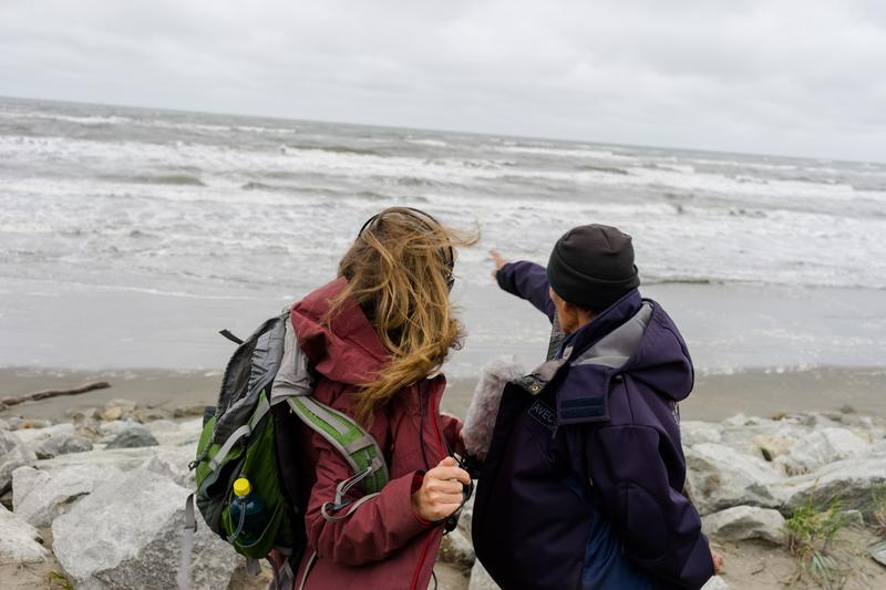 Winfred Obruk (right) from Shishmaref, Alaska shows Amy Martin (right) where the island used to be before erosion, caused in part by climate change, ate away at the island.
