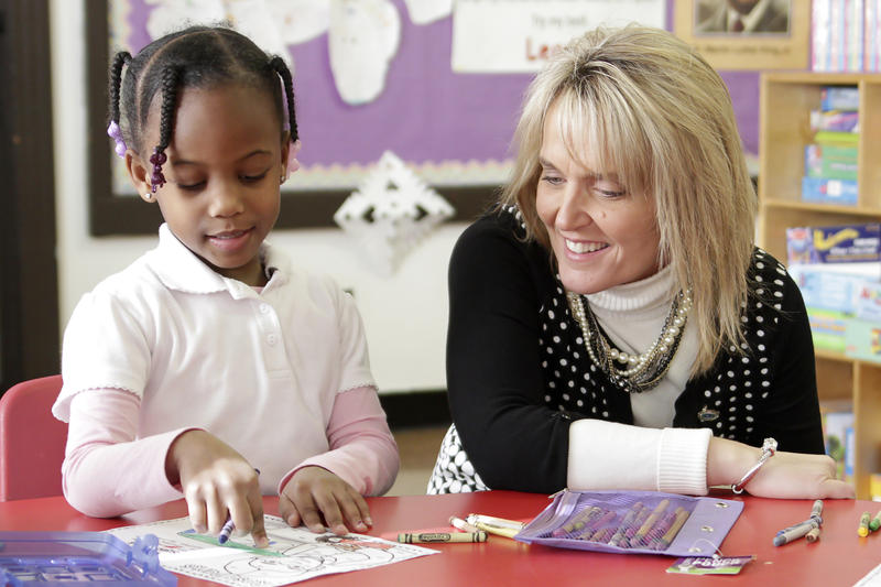 Missouri Education Commissioner Margie Vandeven, right, looks over a student's work during a tour of the Jennings School District.