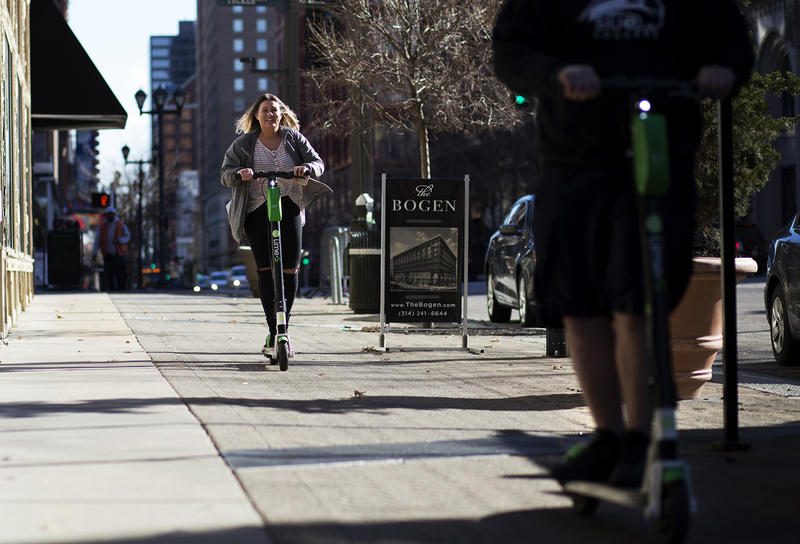 People ride Lime scooters along Washington Avenue in downtown St. Louis Tuesday afternoon. Jan. 8, 2019.
