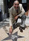 Former Congressman Bill Clay kneels by his star on the Walk of Fame. (UPI photo/Bill Greenblatt)