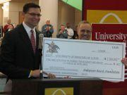 Anheuser-Busch president David Peacock presents a $2.5 million check to UMSL Chancellor Thomas George.