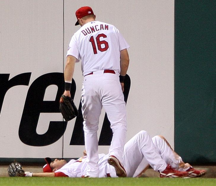 St. Louis Cardinals Chris Duncan stands over teammate Rick Ankiel, who crashed into the center field wall. Ankiel was taken to a hospital.   (UPI Photo/Bill Greenblatt)