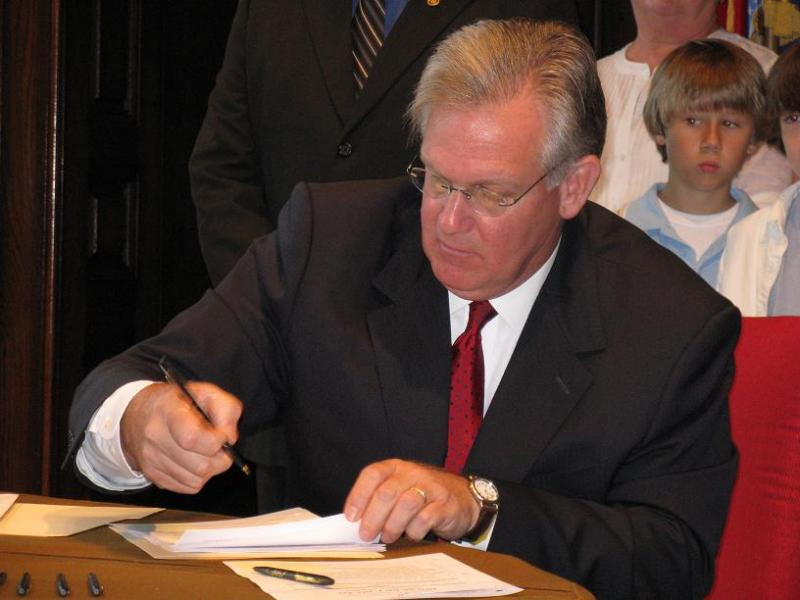 Mo. Gov. Jay Nixon signs a bill into law in his State Capitol office.