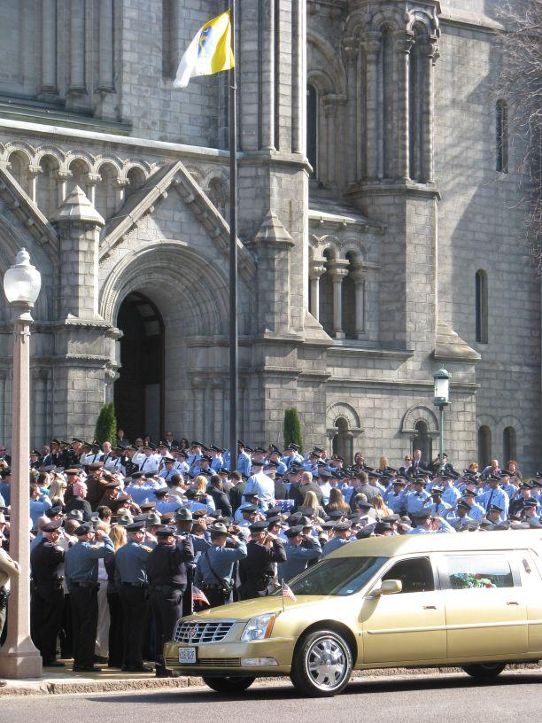 Hundreds of officers salute as the casket of Officer David Haynes is carried into the Cathedral Basilica