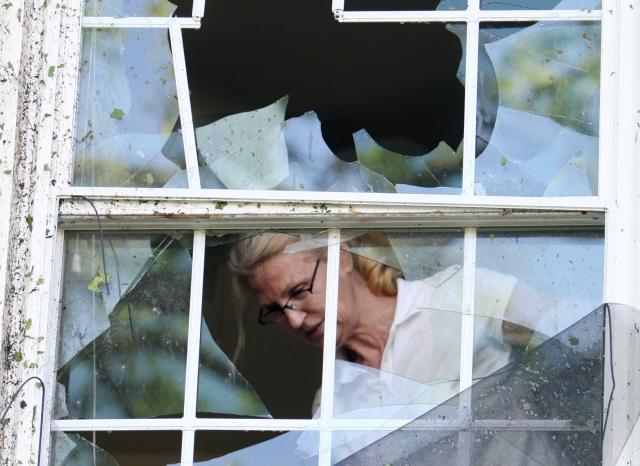 Jeanette Kelly inspects damage to a bedroom window on her home in Des Peres after Saturday's storm. (photo: UPI/Bill Greenblatt)