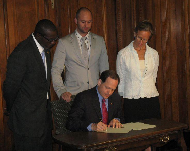 As board president Lewis Reed, Alderman Shane Cohn, and Trailnet's Ann Mack look on, Mayor Francis Slay signs the Complete Streets bill