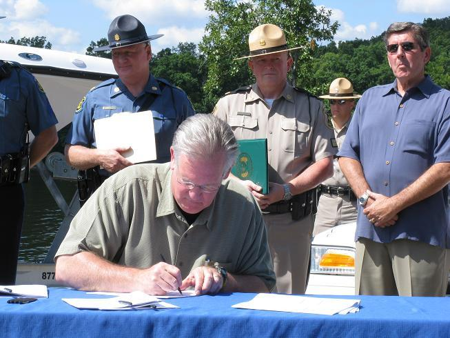 Gov. Jay Nixon signs copies of a bill merging the Missouri State Highway Patrol and the Mo. State Water Patrol at a ceremony at the Lake of the Ozarks.