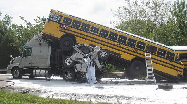 A school bus rests on top of the cab of a tractor trailer following Thursday's fatal chain reaction accident on I-44