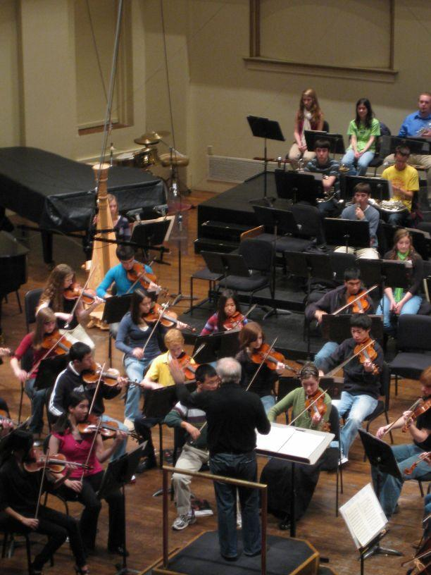 "Leonard Slatkin leads the youth orchestra in a rehearsal of ""Billy the Kid.\"""