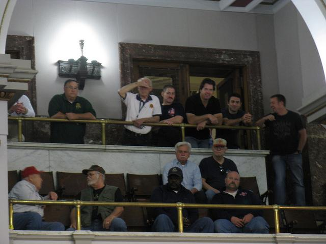 Current and retired firefighters watch the Board of Aldermen debate reforms to their pension system on April 16, 2012.