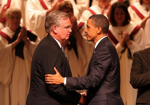 Missouri Governor Jay Nixon (L) greets U.S. President Barack Obama during a memorial service for the dead and missing in Joplin,Missouri on May 29, 2011.