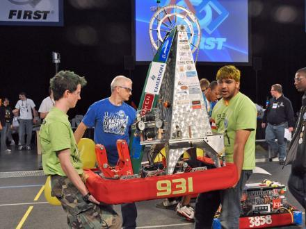 Peter Prombo Cates (left) and Chirag Doshi, students at Gateway Institute of Technology in St. Louis, carry their team's robot off the playing field during the FIRST Robotics Competition regional round in St. Louis in 2011.