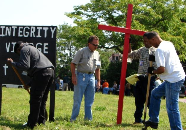 New Life Evangelistic Center workers erect a sign and crucifix on a two-acre plot in Botanical Heights where Rev. Larry Rice plans to host a homeless camp.
