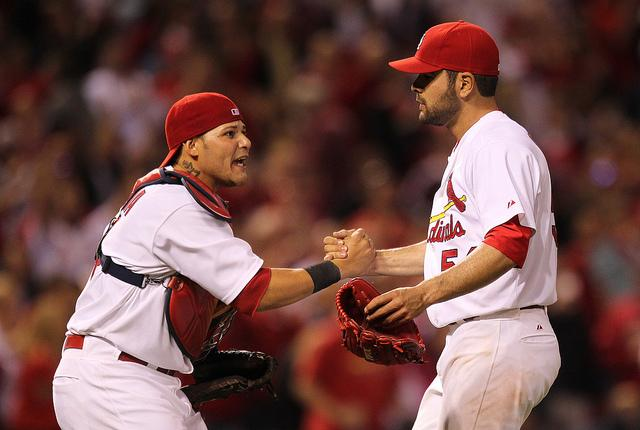 Yadier Molina, shown here, at left, with Jaime Garcia after a May 2011 win against the Milwaukee Brewers, has signed a 5-year, $75 million contract that keeps him in a Cardinals uniform until 2017