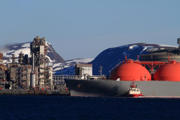 A pilot boat pushes the enormous tanker ship, Arctic Voyager, into position for loading of liquefied natural gas at the unique facility in Hammerfest.  The facility is fed by a borehole hidden 90 miles offshore in the Barents Sea, 1000 feet beneath the surface.
