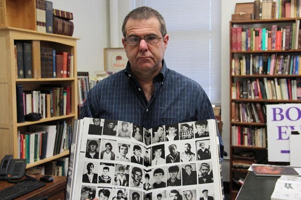 Fontbonne University professor Benjamin Moore holds a book with photos of Muslims who lost their lives during the Bosnian War.