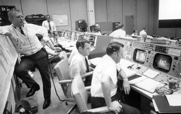 Apollo 11 flight directors Gene Kranz (left), Glynn Lunney (center) and Cliff Charlesworth watch on the monitors in Mission Control as astronauts Neil Armstrong and Buzz Aldrin walk on the surface of the moon.