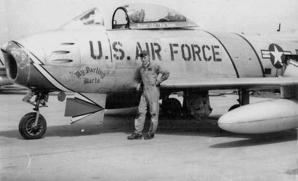 "Kranz poses in front of the F-86 Sabre he flew as part of the U.S. Air Force 69th Fighter Bomber Squadron in Korea. He named his plane ""My Darling Marta"" after his wife, Marta Cadena. She sewed the white vests Kranz was known for wearing as flight director during his NASA missions."