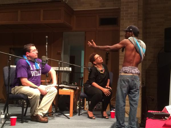 An audience member shows Ferguson Mayor James Knowles III a rubber bullet wound that he says he received during unrest in the north St. Louis County city. A forum sponsored by St. Louis Public Radio became heated, with the biggest ire being directed at Knowles. NPR's Michel Martin is at center.