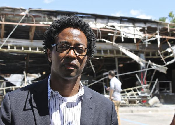 On Tuesday, Wesley Bell and colleagues handed out college enrollment postcards at the burned out QuikTrip. Bell says it is important to reach out to young people who are feeling disenfranchised.