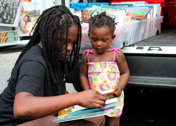Lavonda Logwood and 2 year old Lei'onna Hawthorne look for books about animals from the Sweet Reads truck.