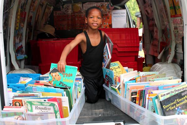 6 year old Latrell Thomas digs through bins of books. He says his favorite books are about Star Wars.