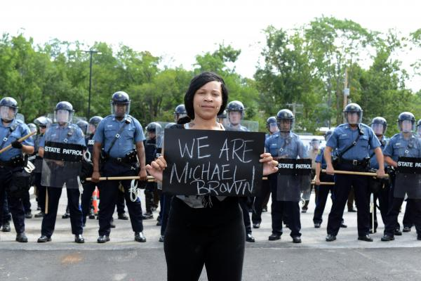 Arianna Whiteside stands in front of police officers in riot gear during a protest march to the Ferguson Police Department on Aug. 11.