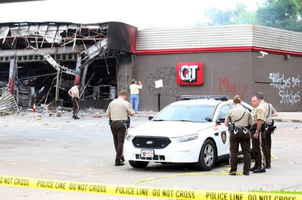 Members of the St. Louis County Police Department remain on the lot of the QuikTrip Gas station in Ferguson, Missouri on August 11, 2014.