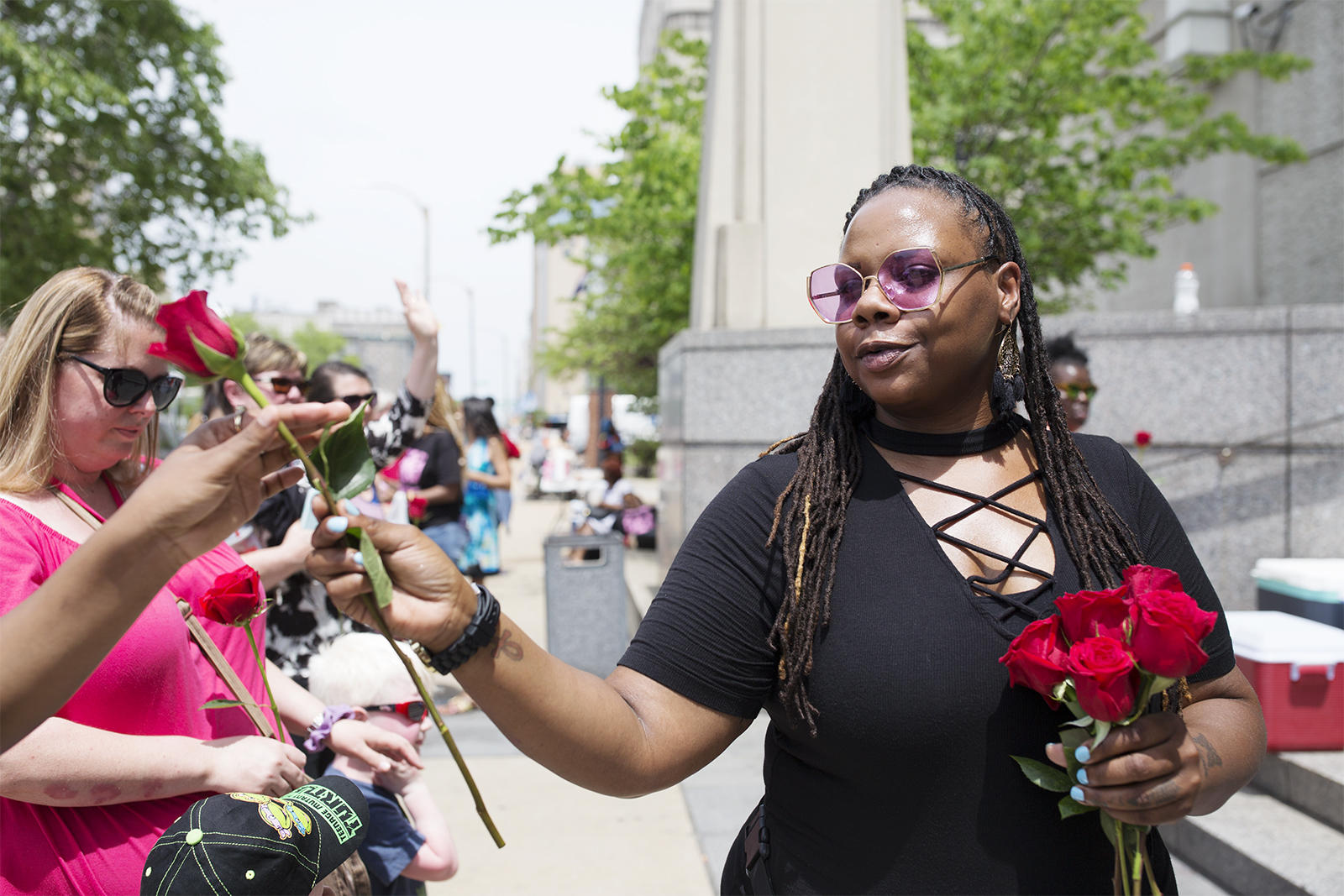 Melanie Randels who helped organized the Expect Us Mother's Day bail out hands out flowers to mothers outside the St. Louis City Justice Center