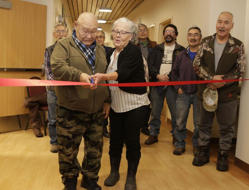 James Charlie Sr., YKHC Honorary Board Member, and Gloria Simeon, YKHC Board Vice Chair, perform the ribbon cutting ceremony at the opening of the Yukon Kuskokwim Ayagnirvik Healing Center on January 11, 2017, surrounded by YKHC board members.