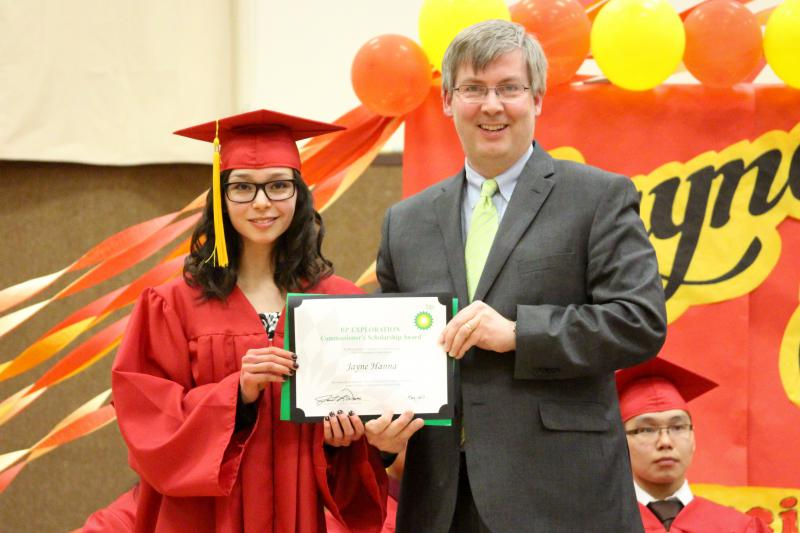 Bob Williams, the Director of the Division of Educator and School Excellence for the Alaska Department of Education & Early Development, presents Jayne Hanna with her BP Scholarship Awards at her graduation ceremony in Mekoryuk on May 12, 2017.