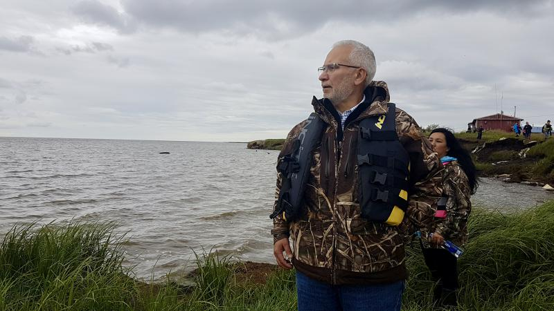 Carlton Kuhns, Assistant Superintendent to the Lower Kuskokwim School District, walks along a debris strewn shoreline of Newtok to the boats headed for Mertarvik.
