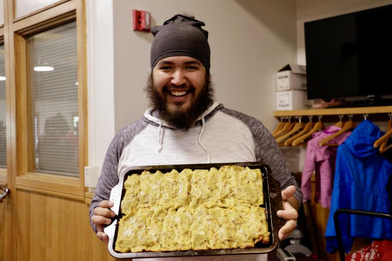 Andrew Gonzales holds up a tray of his vegan enchiladas, paired with rice and beans.