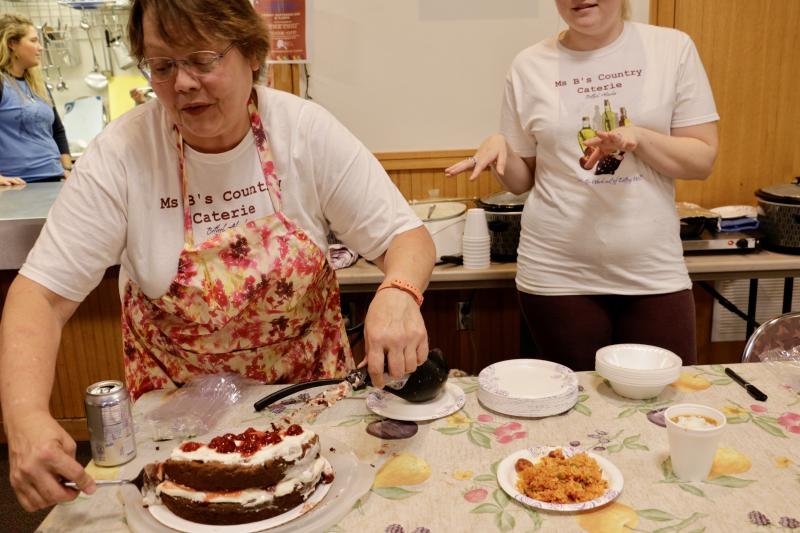 Samatha Buckley, with Ms B's Country Catering, cuts another slice of her Italian Crème Cake.