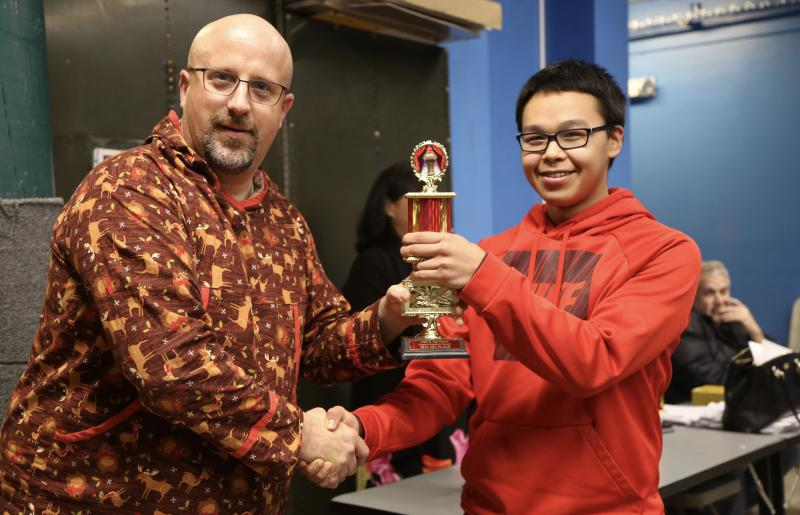 LKSD Director of Personnel and Student Services Josh Gill hands Jakob Sipary of Napaskiak his first place trophy for English Expository Speaking on December 13, 2017.