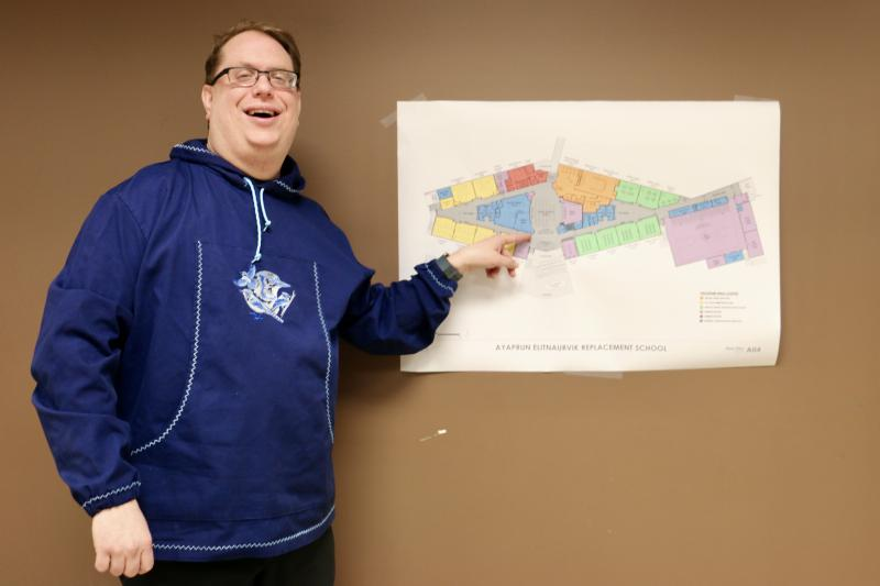 Ayaprun Elitnaurvik Principal Zachary Bastoky stands at the school's current location in the Kipusvik Center next to the floor plans proposed new school building, December 7, 2017.
