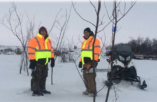 Perry Barr and Jeff Evon mark open holes with willows and blue reflectors on the Kuskokwim near Bethel on December 17, 2017.