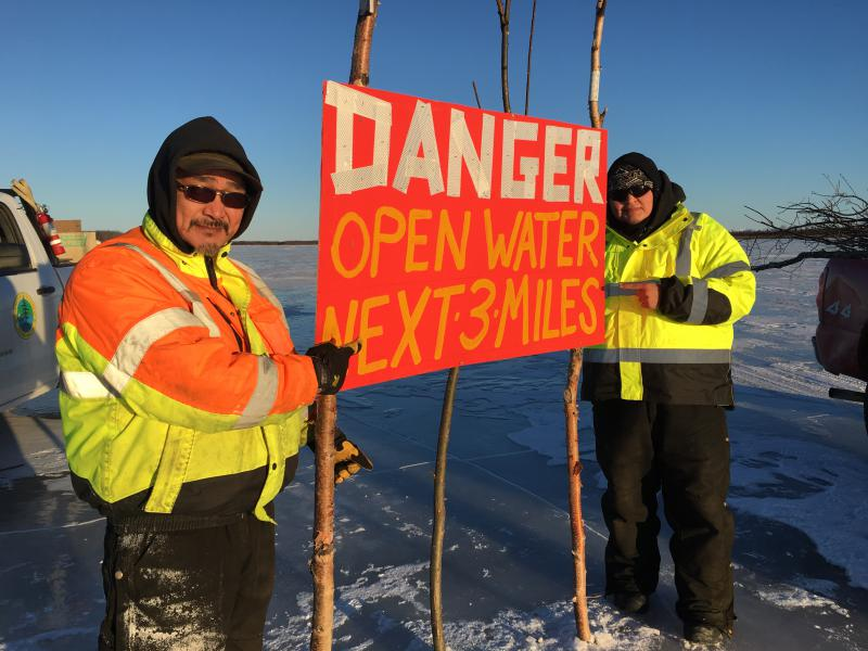 Seraphim Evan and Stanley Morgan of Kalskag pose near a marked hole on the ice road.