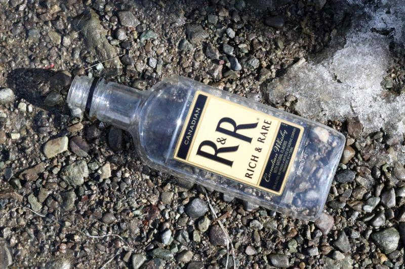 A bottle of R&R Whiskey lying in a Bethel parking lot.