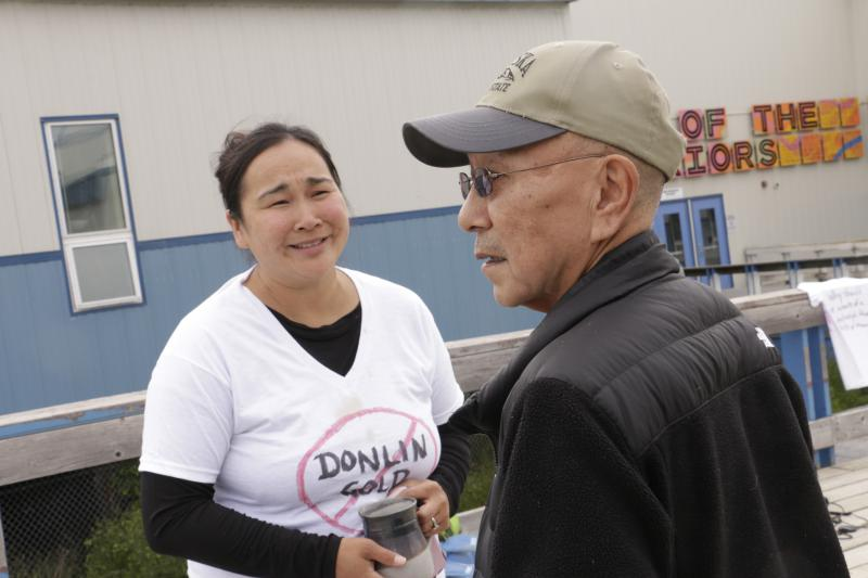 Danielle Craven speaks to John Nick, a shareholder with the Calista Regional Native Corporation, about concerns over the environmental impacts of the proposed Donlin Mine.