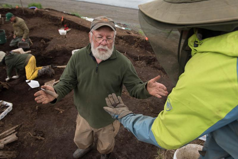 Dr. Rick Knecht explains the purpose of a small triangular piece of leather to student Lauren Phillips while digging at the Nunalleq site on July 24, 2018. The leather is likely caribou hide and was used to patch a larger piece of hide or clothing.