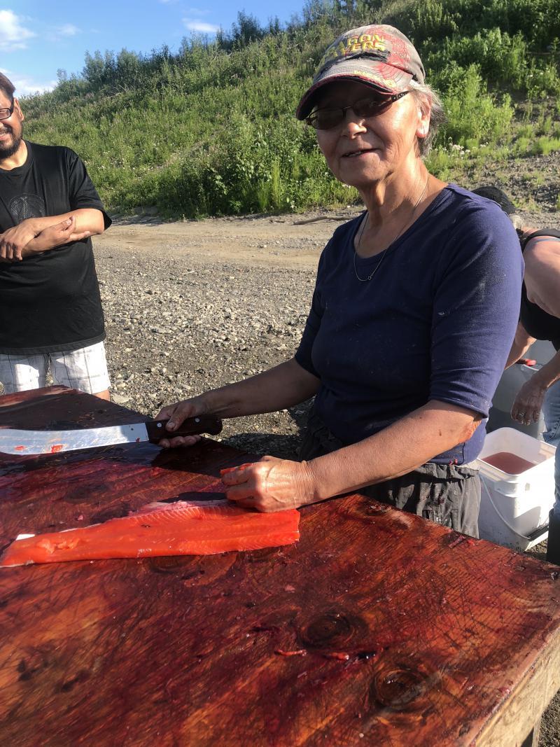 Francine Kvamme's cutting her fish at the Kuskokwim River.